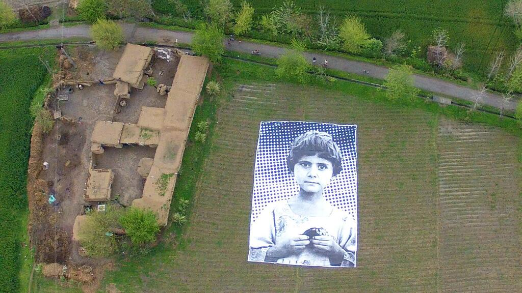 "In April 2014, a group of activists and artists installed this enormous poster in a field in Pakistan to stare up at the remote operators of unmanned aerial vehicles. The image is of a child reportedly orphaned in a 2009 drone strike. The ""Not A Bug Splat"" art project is the work of Pakistanis, Americans and the French street artist JR, and illustrates the transmedia context – poster, Web, surveillance cameras, etc. – of contemporary image engagement. (Photo courtesy of notabugsplat.com)"
